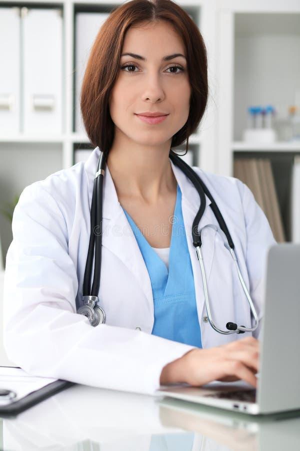 Glückliche Brunetteärztin, die am Tisch sitzt und herauf Krankengeschichteform füllt lizenzfreie stockfotografie