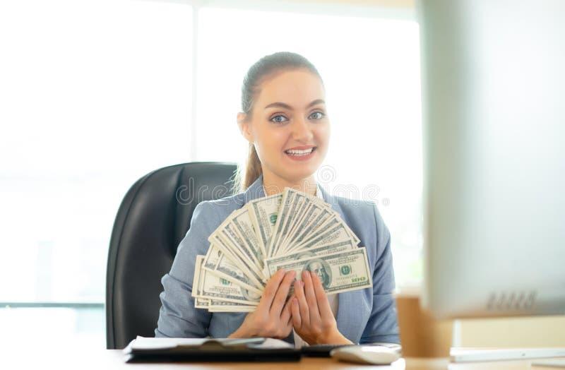 Glückliche brunette Frau mit vielen Dollar nahe Laptop im Büro lizenzfreie stockfotos