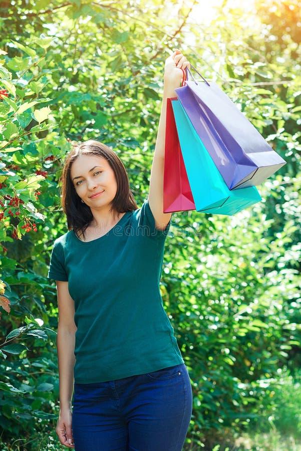 Glückliche brunette Frau nach den großen Einkaufsverkäufen, bunte Einkaufstaschen halten stockbild