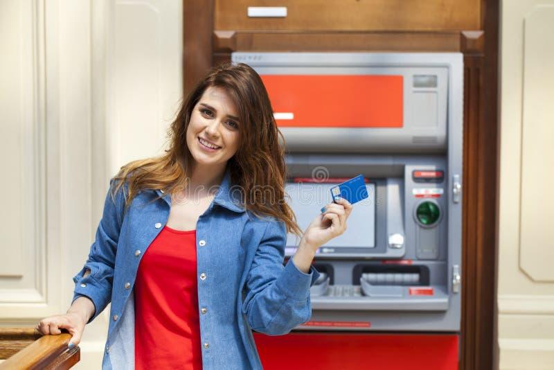 Glückliche Brunettefrau, die Geld von der Kreditkarte an ATM zurücknimmt stockbild
