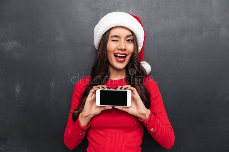 Glückliche Brunettefrau im roten Blusen- und Weihnachtshut stockbilder