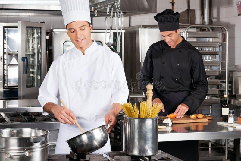 Glückliche Chefs, die Lebensmittel zubereiten lizenzfreie stockbilder