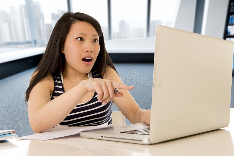 Glückliche chinesische asiatische Frau, die an ihrem Computer sitzt am modernen Schreibtischlächeln nett arbeitet und studiert lizenzfreie stockfotografie