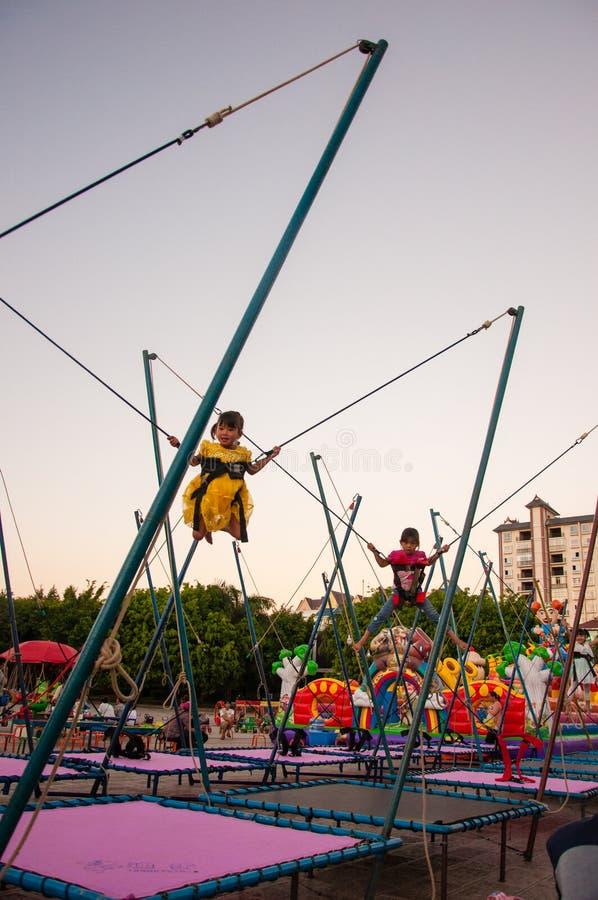 Glückliche chinesische Kinder, die Schwingen-Spiel spielen stockfotografie