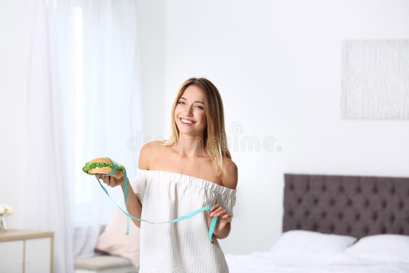 Glückliche dünne Frau mit messendem Band und Burger lizenzfreies stockfoto