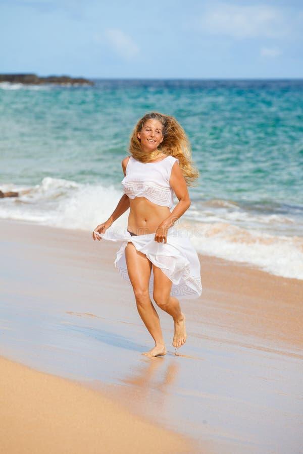 Glückliche Dame, die auf dem Strand trainiert stockbilder