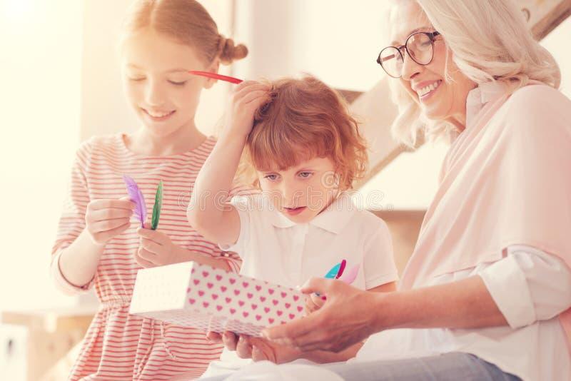 Glückliche Dame im Ruhestand, die Freizeit mit Kindern genießt stockfotografie