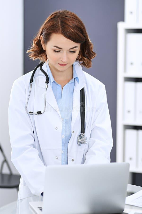 Glückliche Doktorfrau bei der Arbeit Porträt des weiblichen Arztes, der Laptop-Computer bei der Stellung des nahen Aufnahmeschrei stockfoto