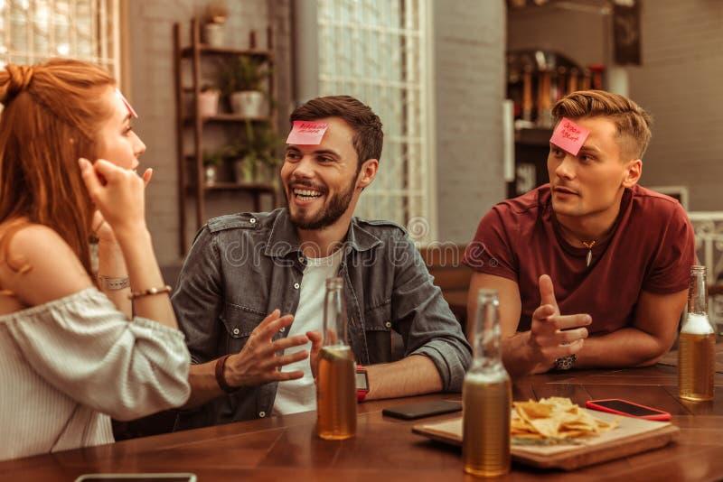 Glückliche drei Freunde, die ein Lachen teilen und zusammen hedbanz spielen stockbilder