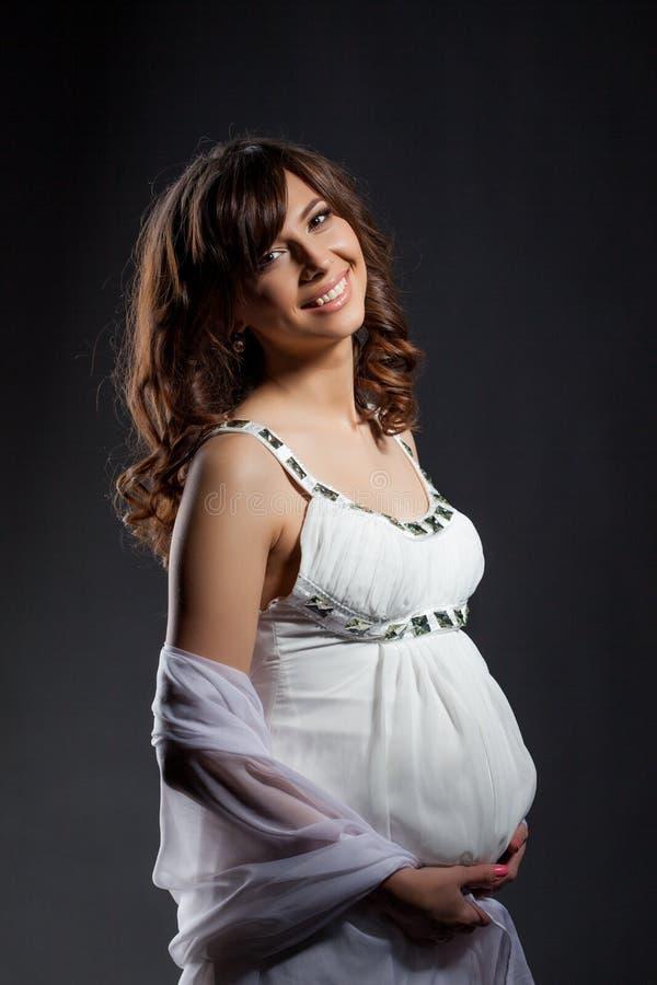 Glückliche dunkelhaarige schwangere Frau, die an der Kamera lächelt stockfotografie