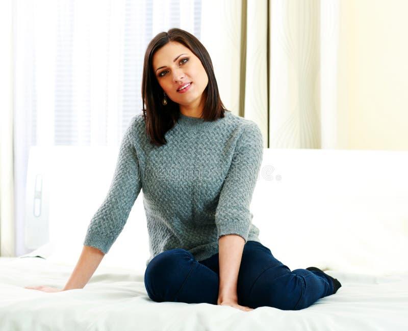 Glückliche durchdachte Frau von mittlerem Alter, die auf dem Bett sitzt stockbild