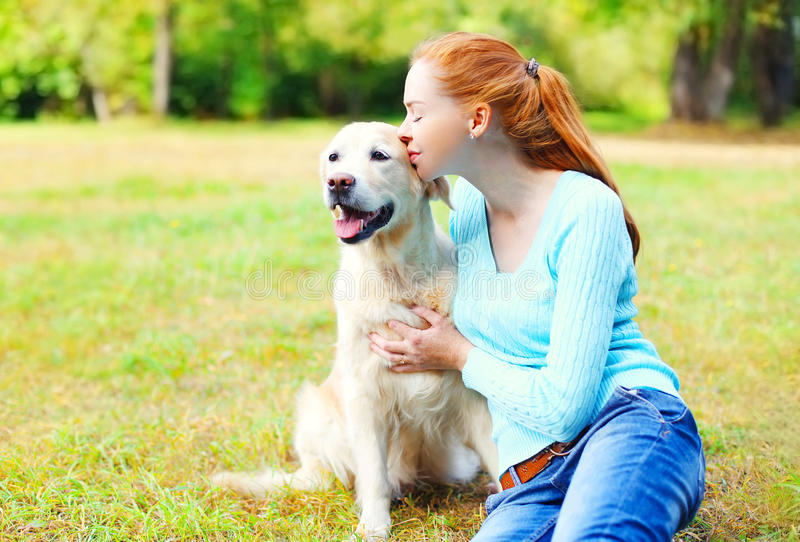 Glückliche Eigentümerfrau, die golden retriever-Hund küsst lizenzfreies stockfoto