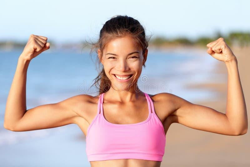 Glückliche Eignungs-Frau, die Muskeln auf Strand biegt - stockbilder