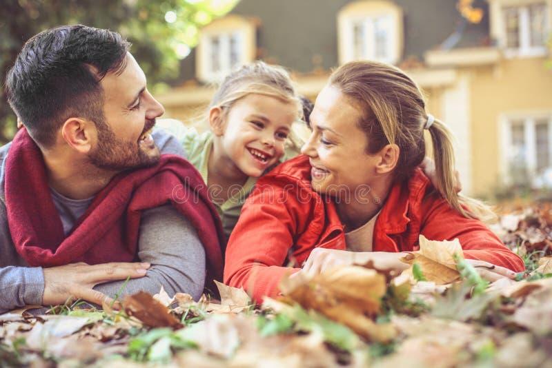 Glückliche Eltern, die am Hinterhof mit Kind niederlegen stockbilder