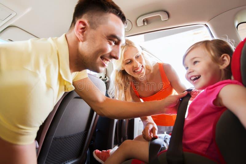 Glückliche Eltern, die Kind mit AutoSicherheitsgurt befestigen stockfotografie