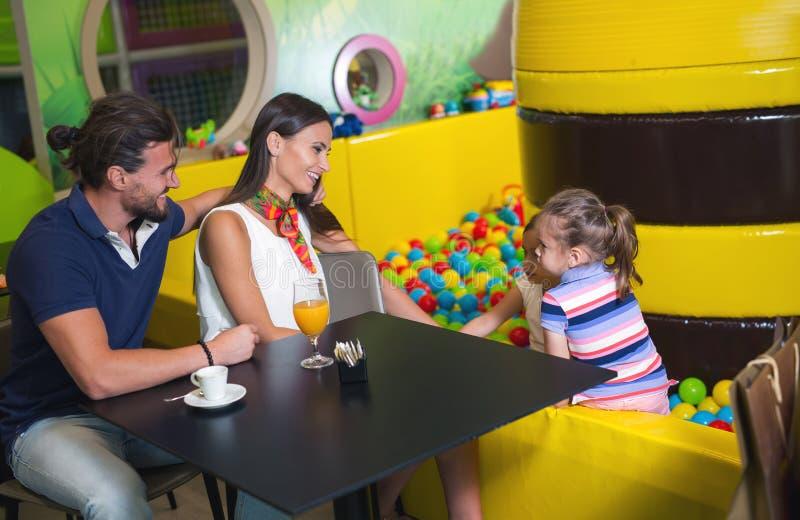 Glückliche Eltern, die Spaß mit Kindern im Kinderspielplatz haben lizenzfreie stockfotos