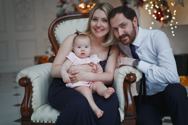 Glückliche Eltern mit Baby in verziertem Raum für Weihnachten stockbilder