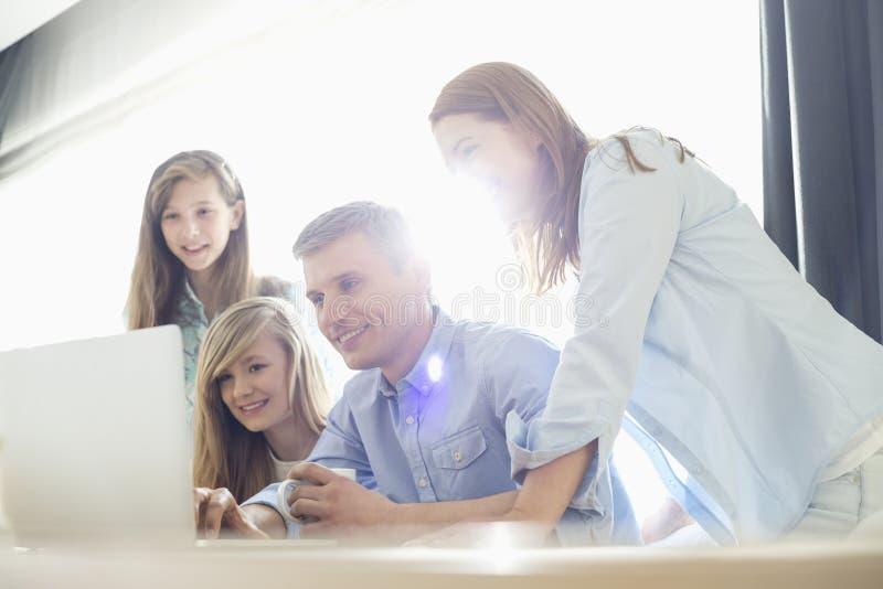 Glückliche Eltern mit den Töchtern, die zu Hause Laptop verwenden lizenzfreie stockfotografie