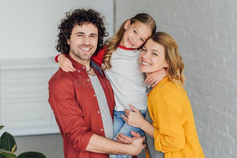 glückliche Eltern mit der entzückenden kleinen umarmenden und lächelnden Tochter lizenzfreies stockbild