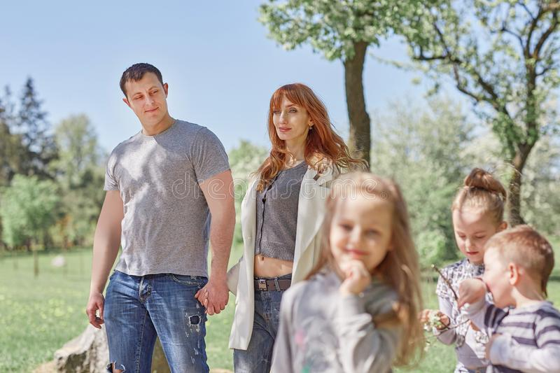 Glückliche Eltern mit Kindern auf einem Weg im Park stockbilder
