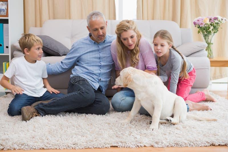 Glückliche Eltern und ihre Kinder auf Boden mit Welpen lizenzfreies stockfoto
