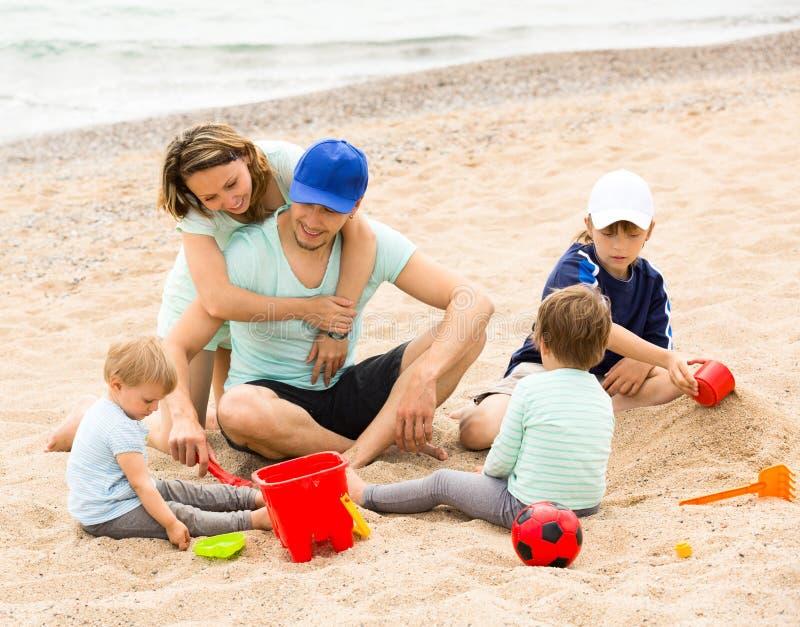 Glückliche Eltern und Kinder, die mit Sand spielen stockbilder