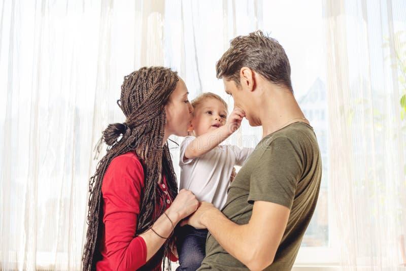 Glückliche Eltern Vater und Mutter, die mit Babysohn an auf Fensterhintergrund spielen Nette und moderne junge Familie stockfotografie