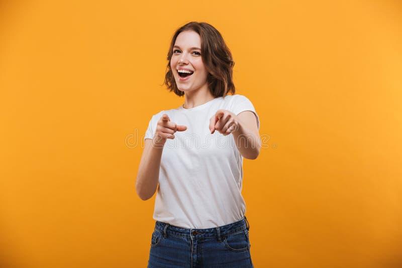 Glückliche emotionale junge Frau, die auf Sie zeigt lizenzfreies stockfoto