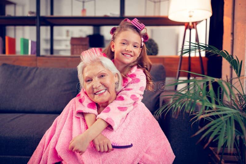 Glückliche Enkelin, die ihre Oma umarmt, nachdem Haarrollen gesetzt worden sind stockbilder