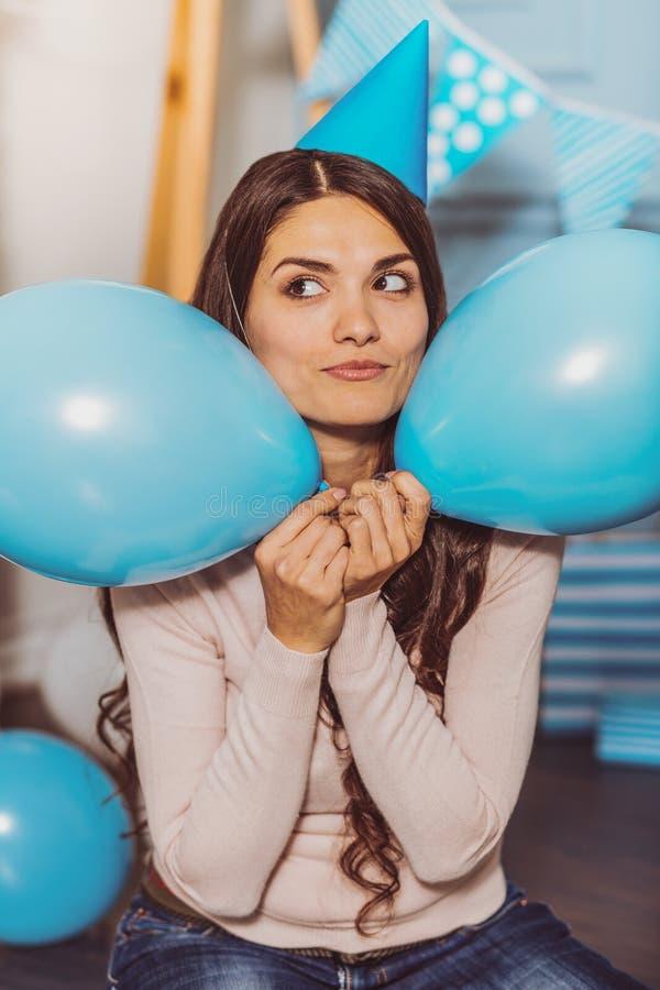 Glückliche enthusiastische Frau, die zwischen Ballonen sich versteckt stockbilder