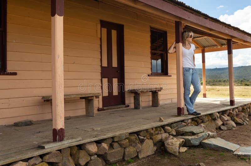 Glückliche entspannte Frau auf Veranda des alten Bauholzhauses in der ländlichen Landschaft stockbilder