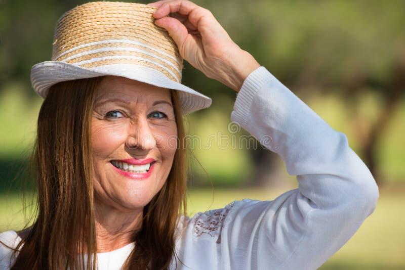 Glückliche entspannte Frau mit Hut im Park draußen lizenzfreies stockbild