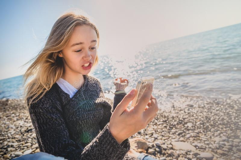 Glückliche entspannte junge Frau, die in einer Yogahaltung am Strand meditiert stockbilder
