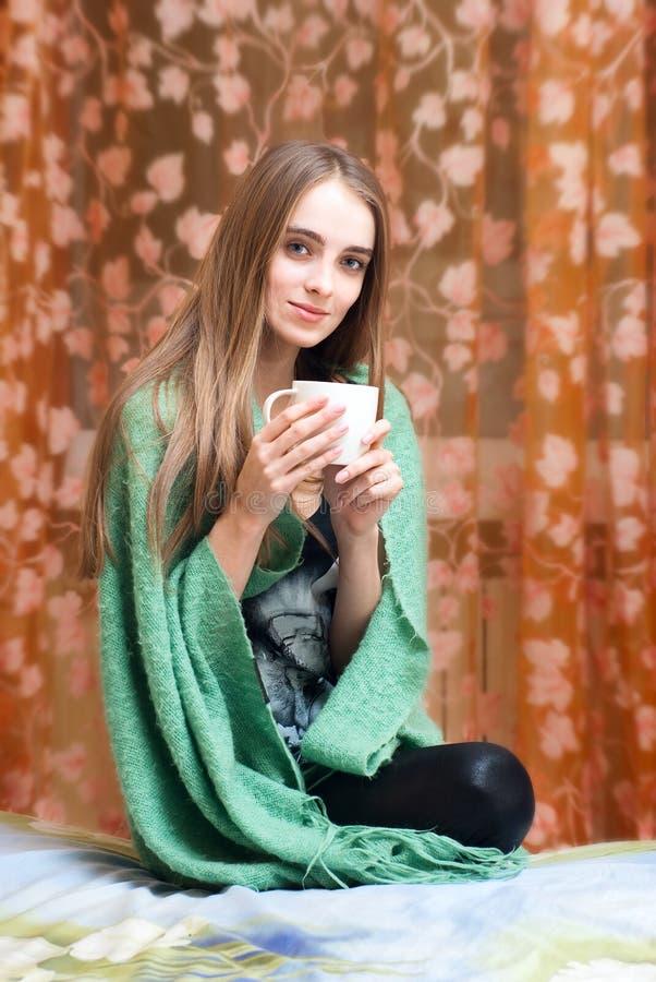 Glückliche entspannte junge Frau, die im Plaid mit Co sitzt lizenzfreies stockfoto