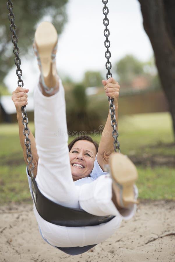 Glückliche entspannte reife Frau auf dem Schwingen im Freien stockfoto