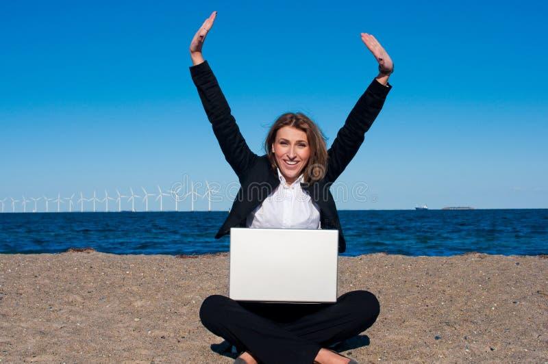 Glückliche erfolgreiche Geschäftsfrau auf dem Strand, vert lizenzfreies stockfoto