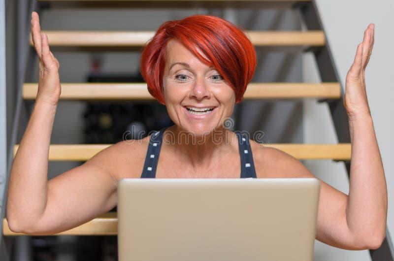 Glückliche erwachsene Frau mit dem Laptop, der ihre Arme anhebt stockfoto