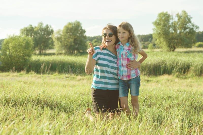 Glückliche erwachsene Mutter, die draußen mit ihrem Tochterkindermädchen spielt Hintergrundnatur, Sommer lizenzfreies stockbild