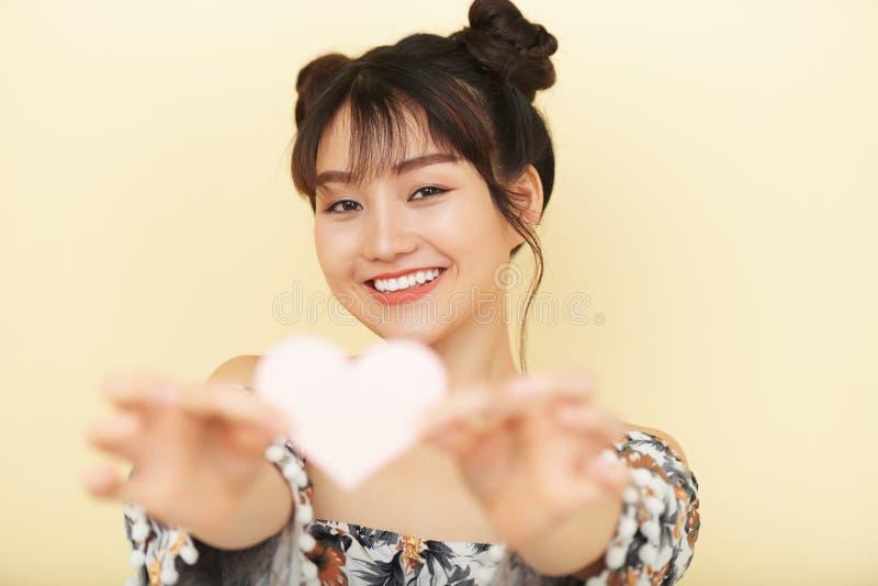 Glückliche ethnische verliebte Frau, die Herz hält stockfotografie