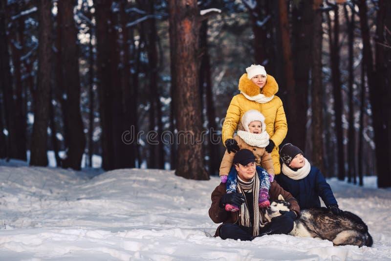 Glückliche europäische junge Familie mit dem großen Hund, der gegen Winterkiefernwald aufwirft stockfotografie