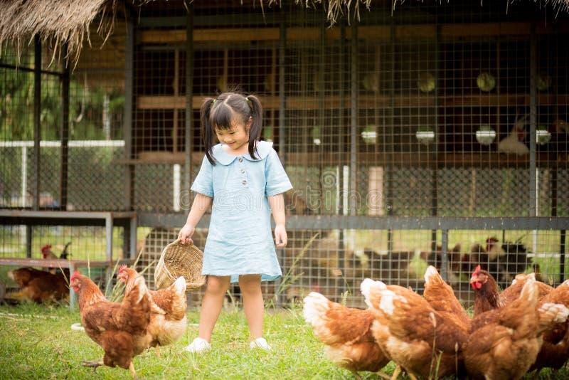 Glückliche Fütterungshühner des kleinen Mädchens vor Hühnerbauernhof lizenzfreie stockfotos
