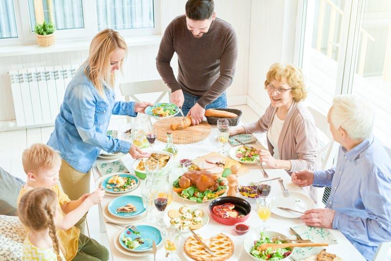 Glückliche Familie am Abendessen im Sonnenlicht lizenzfreies stockfoto
