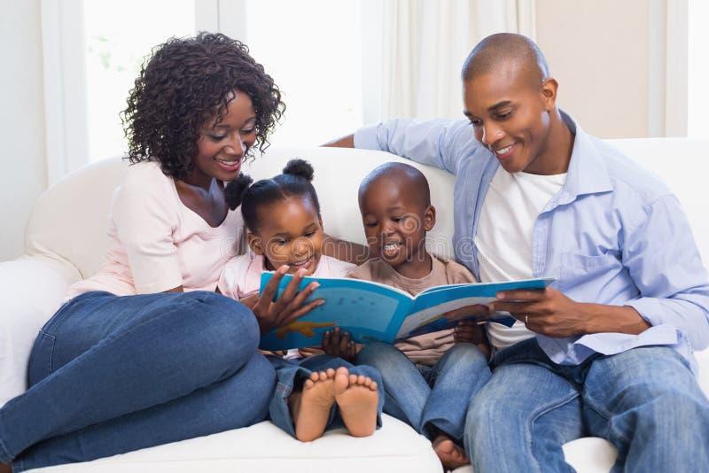 Glückliche Familie auf dem Couchlesemärchenbuch lizenzfreies stockbild