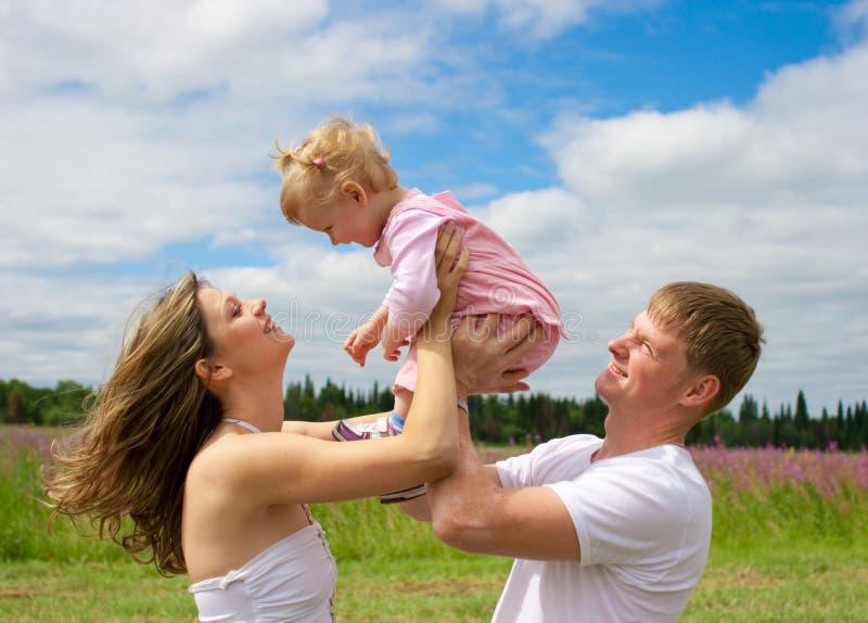 Glückliche Familie auf dem Gebiet oder Wiese im Freien lizenzfreie stockbilder