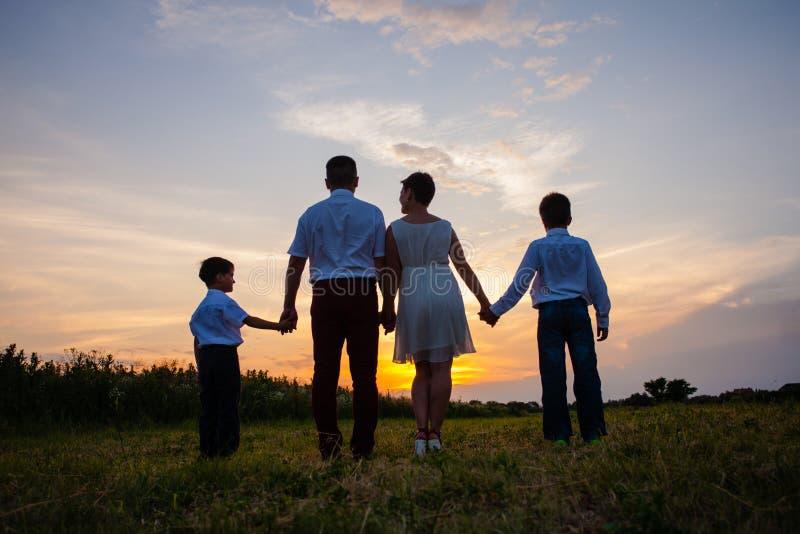 Glückliche Familie auf dem Hintergrund des Sonnenuntergangs stockfoto