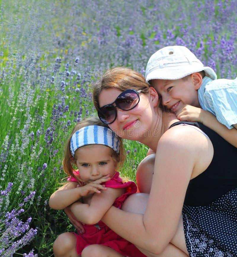 Glückliche Familie auf dem Lavendelgebiet lizenzfreie stockfotos