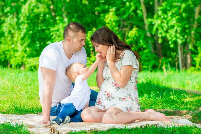 Glückliche Familie auf der Decke, die im Park stillsteht lizenzfreie stockfotos
