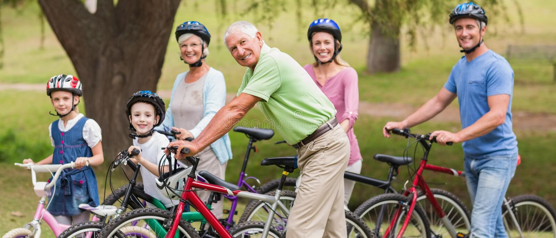 Glückliche Familie auf ihrem Fahrrad am Park stockbild