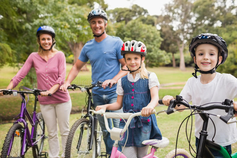 Glückliche Familie auf ihrem Fahrrad am Park lizenzfreie stockfotos