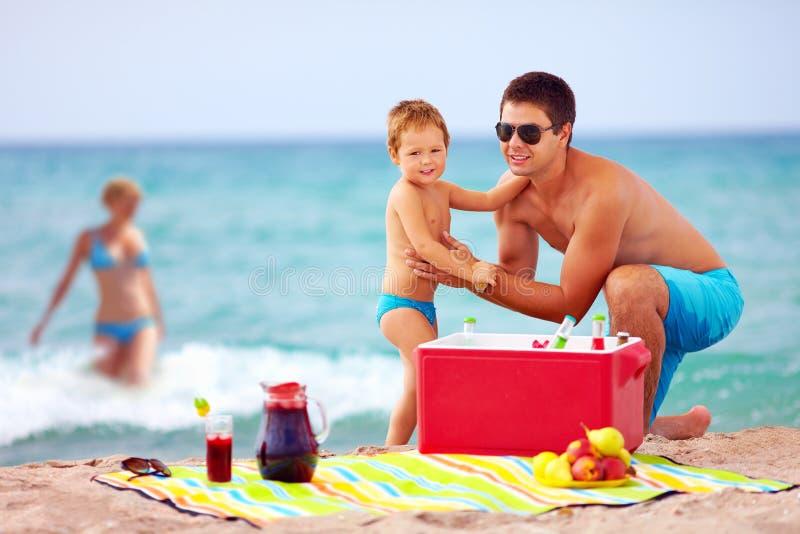 Glückliche Familie auf Sommerstrandpicknick stockbilder
